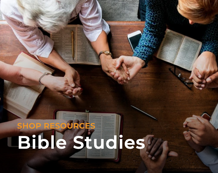 There's a diverse group of people holding hands and praying over their Bibles.