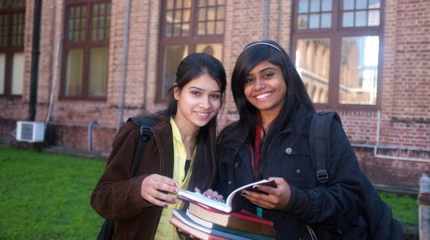 Two teenage girls smiling while holding school books.